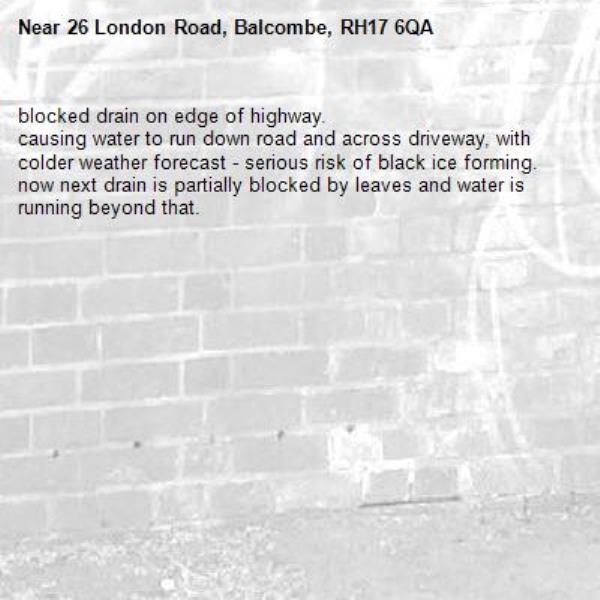 blocked drain on edge of highway. causing water to run down road and across driveway, with colder weather forecast - serious risk of black ice forming. now next drain is partially blocked by leaves and water is running beyond that.-26 London Road, Balcombe, RH17 6QA