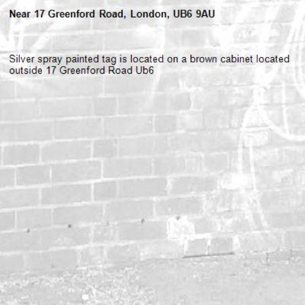 Silver spray painted tag is located on a brown cabinet located outside 17 Greenford Road Ub6 -17 Greenford Road, London, UB6 9AU