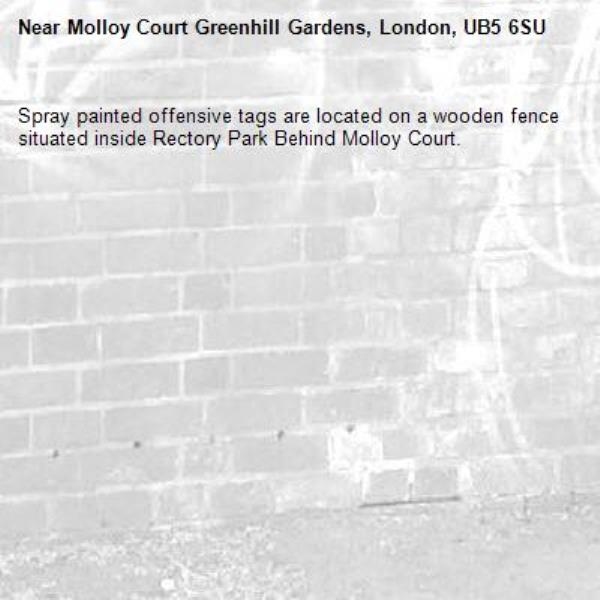 Spray painted offensive tags are located on a wooden fence situated inside Rectory Park Behind Molloy Court. -Molloy Court Greenhill Gardens, London, UB5 6SU