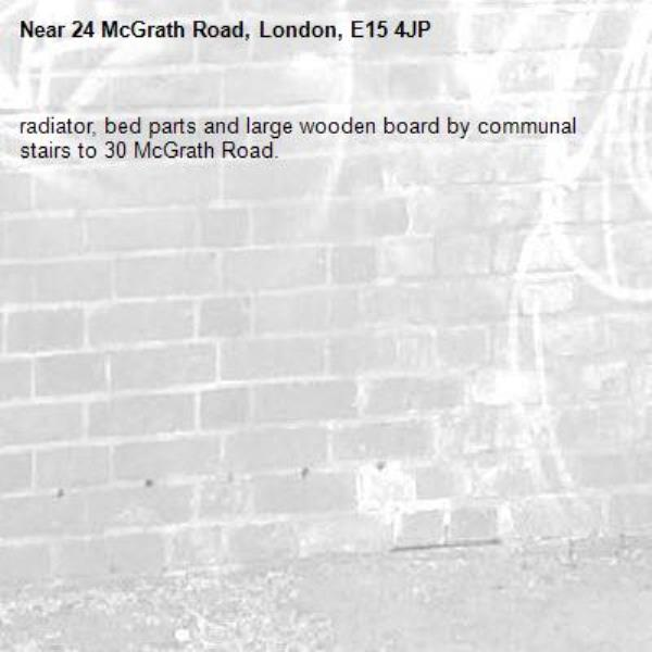 radiator, bed parts and large wooden board by communal stairs to 30 McGrath Road.-24 McGrath Road, London, E15 4JP