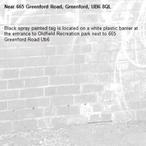 Black spray painted tag is located on a white plastic barrier at the entrance to Oldfield Recreation park next to 665 Greenford Road Ub6 -665 Greenford Road, Greenford, UB6 8QL