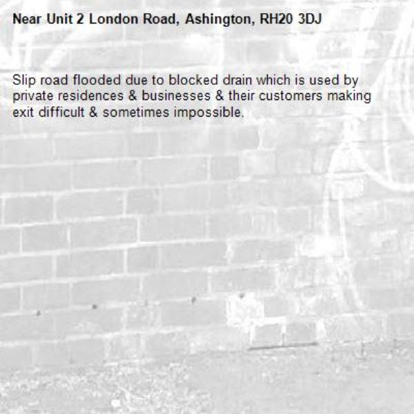Slip road flooded due to blocked drain which is used by private residences & businesses & their customers making exit difficult & sometimes impossible.-Unit 2 London Road, Ashington, RH20 3DJ