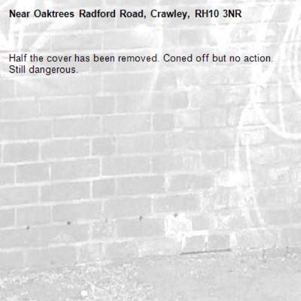 Half the cover has been removed. Coned off but no action. Still dangerous.-Oaktrees Radford Road, Crawley, RH10 3NR