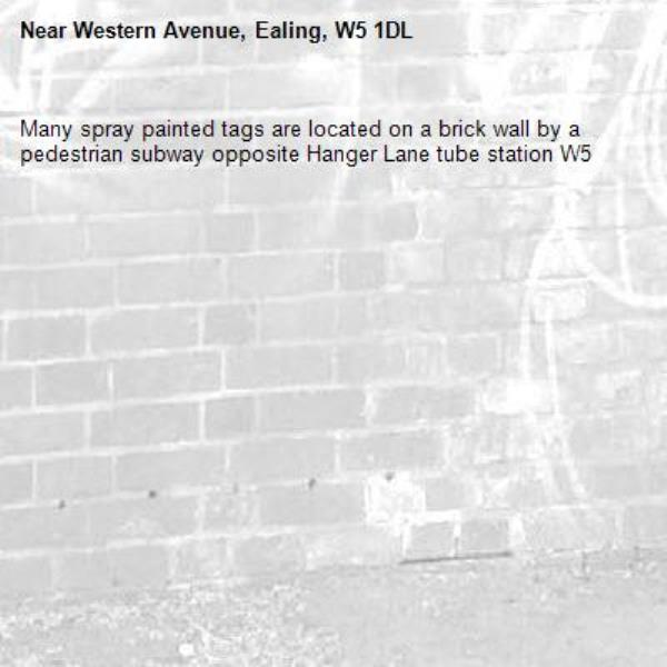 Many spray painted tags are located on a brick wall by a pedestrian subway opposite Hanger Lane tube station W5 -Western Avenue, Ealing, W5 1DL
