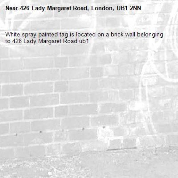 White spray painted tag is located on a brick wall belonging to 428 Lady Margaret Road ub1-426 Lady Margaret Road, London, UB1 2NN
