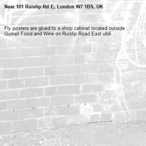 Fly posters are glued to a shop cabinet located outside Gurnell Food and Wine on Ruislip Road East ub6 -101 Ruislip Rd E, London W7 1BS, UK