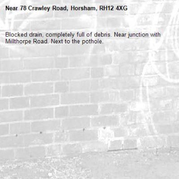 Blocked drain, completely full of debris. Near junction with Millthorpe Road. Next to the pothole.-78 Crawley Road, Horsham, RH12 4XG
