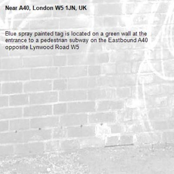 Blue spray painted tag is located on a green wall at the entrance to a pedestrian subway on the Eastbound A40 opposite Lynwood Road W5-A40, London W5 1JN, UK