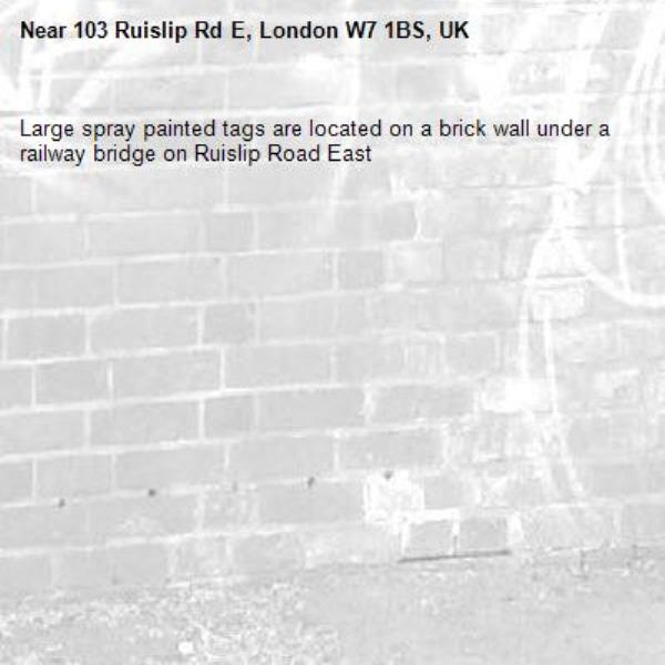 Large spray painted tags are located on a brick wall under a railway bridge on Ruislip Road East -103 Ruislip Rd E, London W7 1BS, UK