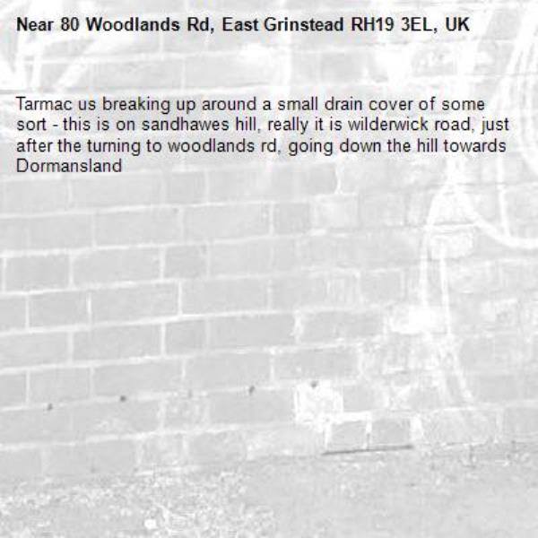 Tarmac us breaking up around a small drain cover of some sort - this is on sandhawes hill, really it is wilderwick road, just after the turning to woodlands rd, going down the hill towards Dormansland-80 Woodlands Rd, East Grinstead RH19 3EL, UK