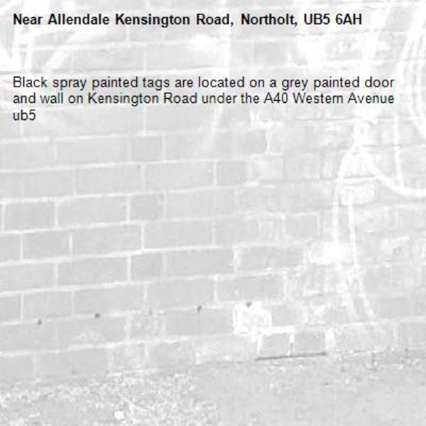 Black spray painted tags are located on a grey painted door and wall on Kensington Road under the A40 Western Avenue ub5-Allendale Kensington Road, Northolt, UB5 6AH