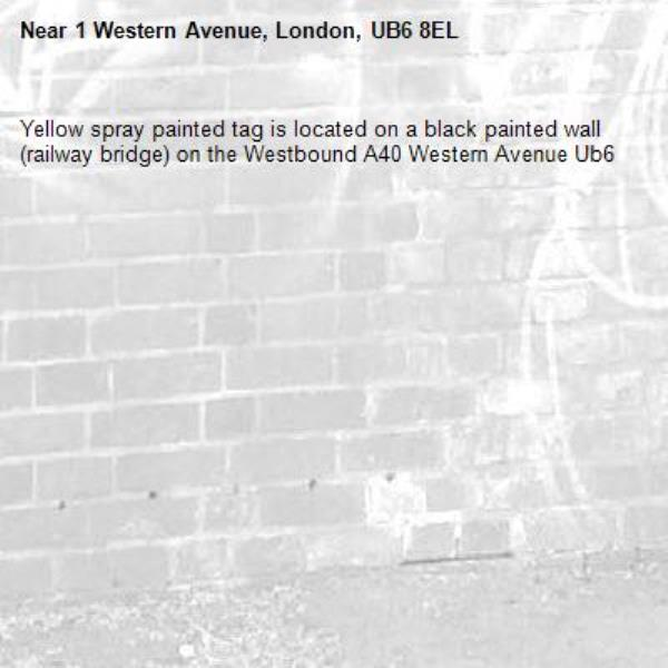 Yellow spray painted tag is located on a black painted wall (railway bridge) on the Westbound A40 Western Avenue Ub6 -1 Western Avenue, London, UB6 8EL