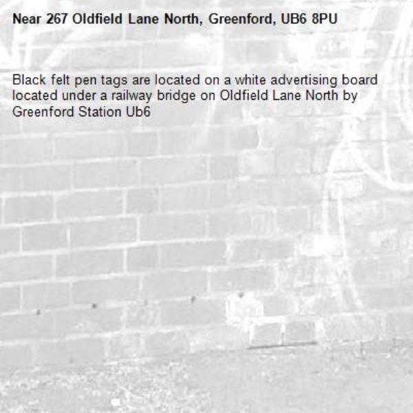 Black felt pen tags are located on a white advertising board located under a railway bridge on Oldfield Lane North by Greenford Station Ub6 -267 Oldfield Lane North, Greenford, UB6 8PU