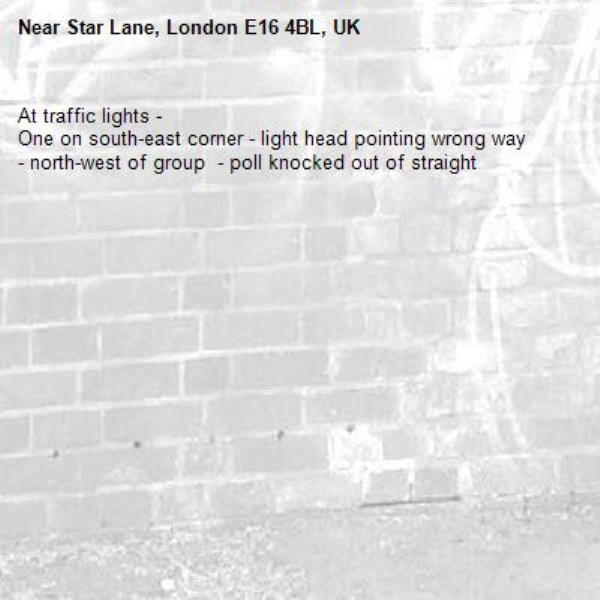 At traffic lights - One on south-east corner - light head pointing wrong way - north-west of group  - poll knocked out of straight-Star Lane, London E16 4BL, UK