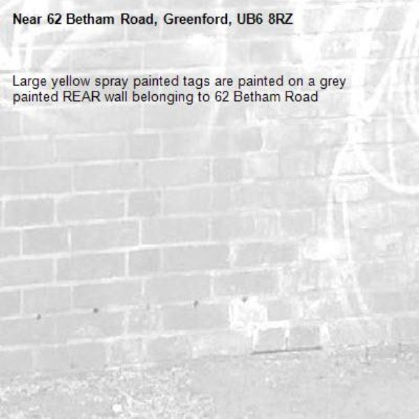 Large yellow spray painted tags are painted on a grey painted REAR wall belonging to 62 Betham Road -62 Betham Road, Greenford, UB6 8RZ