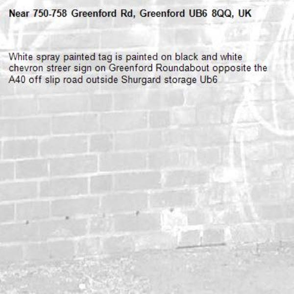White spray painted tag is painted on black and white chevron streer sign on Greenford Roundabout opposite the A40 off slip road outside Shurgard storage Ub6 -750-758 Greenford Rd, Greenford UB6 8QQ, UK