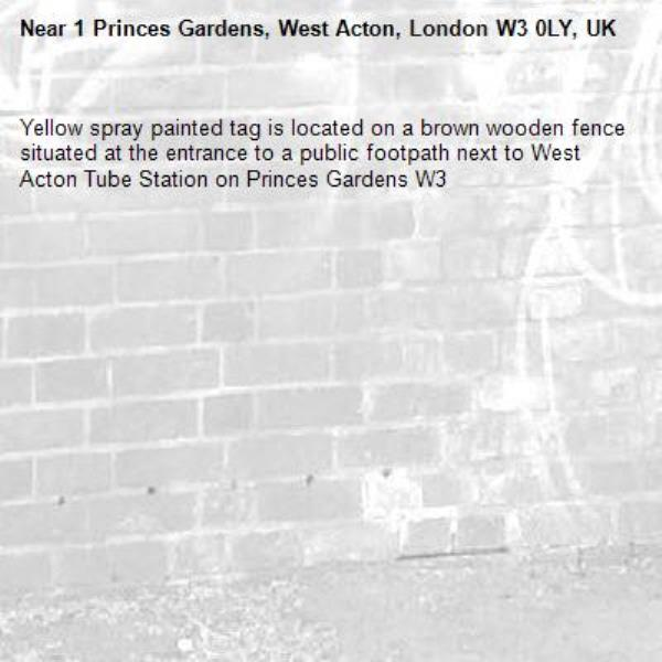 Yellow spray painted tag is located on a brown wooden fence situated at the entrance to a public footpath next to West Acton Tube Station on Princes Gardens W3-1 Princes Gardens, West Acton, London W3 0LY, UK