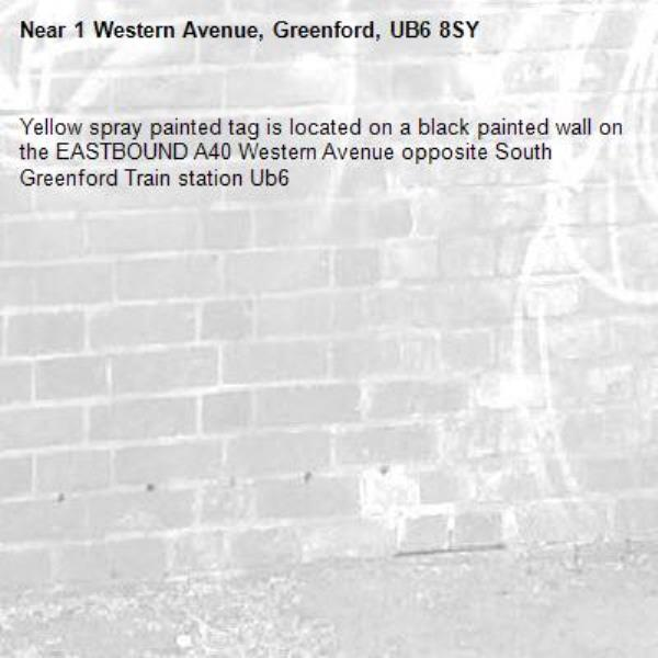 Yellow spray painted tag is located on a black painted wall on the EASTBOUND A40 Western Avenue opposite South Greenford Train station Ub6 -1 Western Avenue, Greenford, UB6 8SY