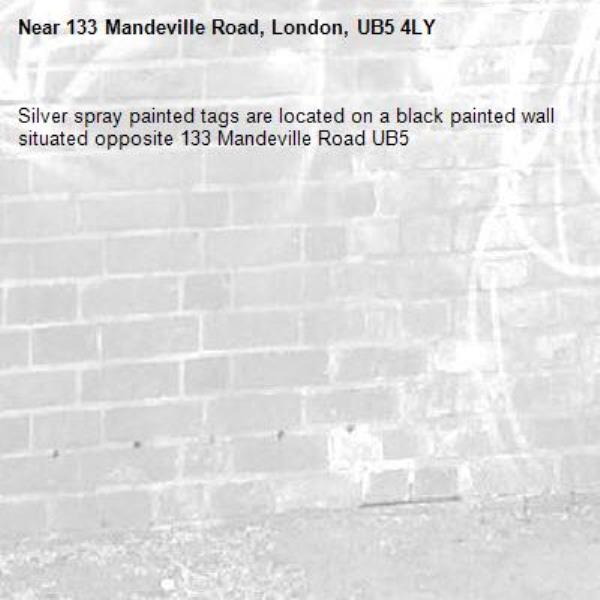 Silver spray painted tags are located on a black painted wall situated opposite 133 Mandeville Road UB5 -133 Mandeville Road, London, UB5 4LY