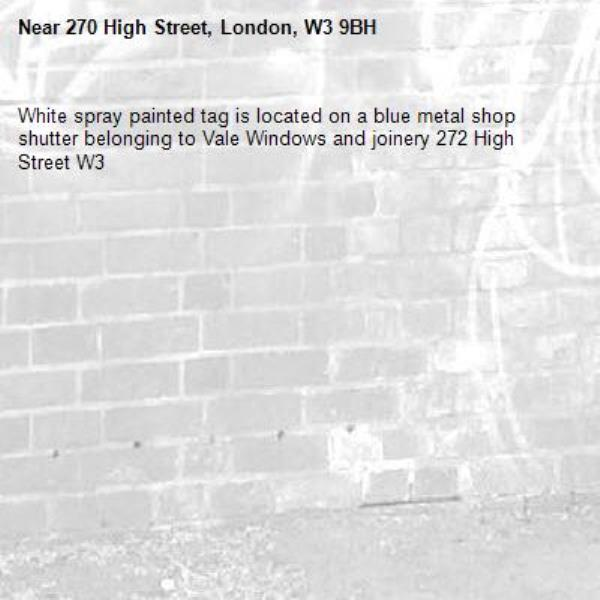 White spray painted tag is located on a blue metal shop shutter belonging to Vale Windows and joinery 272 High Street W3 -270 High Street, London, W3 9BH
