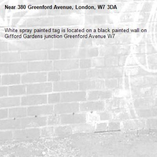 White spray painted tag is located on a black painted wall on Gifford Gardens junction Greenford Avenue W7 -380 Greenford Avenue, London, W7 3DA