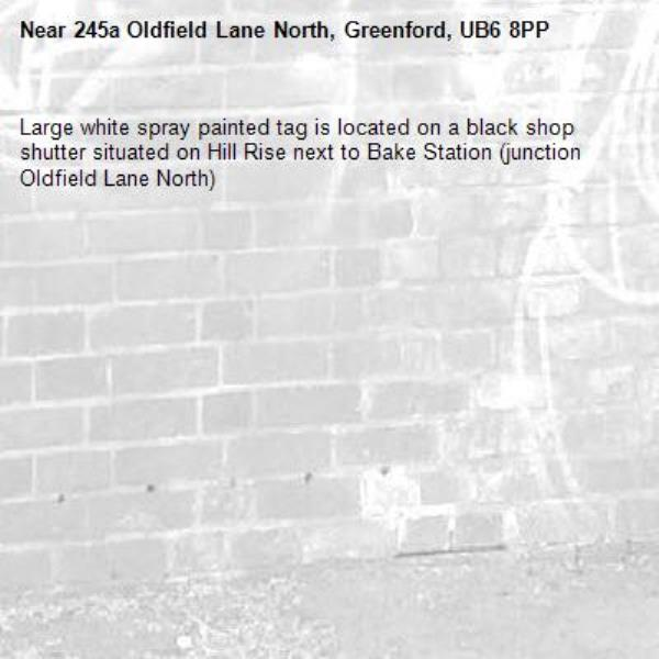 Large white spray painted tag is located on a black shop shutter situated on Hill Rise next to Bake Station (junction Oldfield Lane North) -245a Oldfield Lane North, Greenford, UB6 8PP
