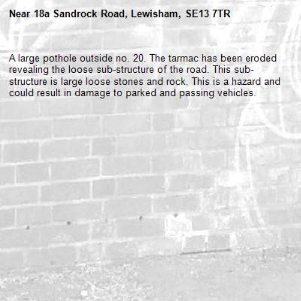 A large pothole outside no. 20. The tarmac has been eroded revealing the loose sub-structure of the road. This sub-structure is large loose stones and rock. This is a hazard and could result in damage to parked and passing vehicles. -18a Sandrock Road, Lewisham, SE13 7TR
