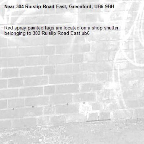 Red spray painted tags are located on a shop shutter belonging to 302 Ruislip Road East ub6 -304 Ruislip Road East, Greenford, UB6 9BH