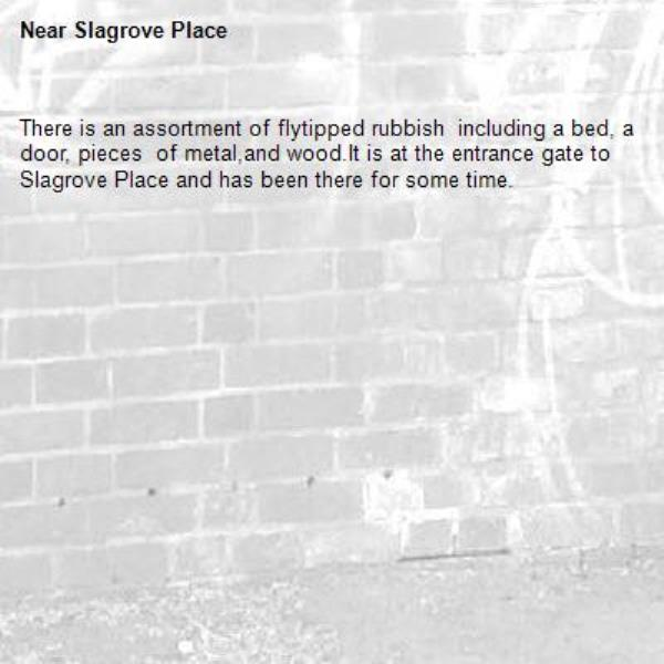 There is an assortment of flytipped rubbish  including a bed, a door, pieces  of metal,and wood.It is at the entrance gate to Slagrove Place and has been there for some time.-Slagrove Place