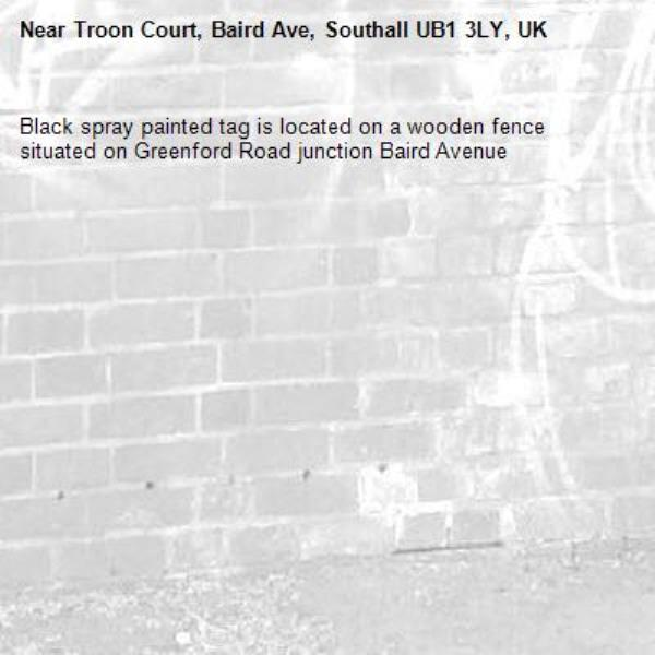 Black spray painted tag is located on a wooden fence situated on Greenford Road junction Baird Avenue -Troon Court, Baird Ave, Southall UB1 3LY, UK