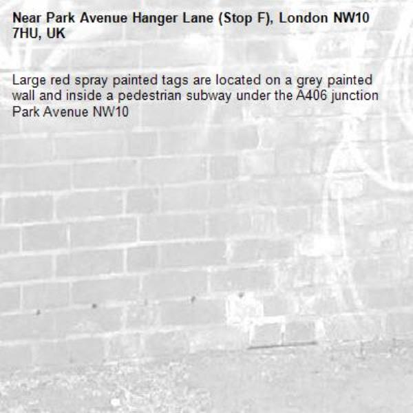 Large red spray painted tags are located on a grey painted wall and inside a pedestrian subway under the A406 junction Park Avenue NW10 -Park Avenue Hanger Lane (Stop F), London NW10 7HU, UK