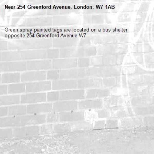 Green spray painted tags are located on a bus shelter opposite 254 Greenford Avenue W7 -254 Greenford Avenue, London, W7 1AB