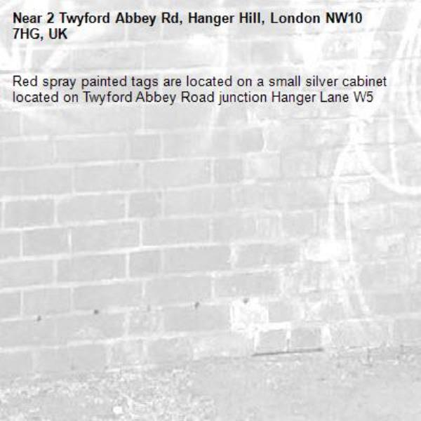 Red spray painted tags are located on a small silver cabinet located on Twyford Abbey Road junction Hanger Lane W5 -2 Twyford Abbey Rd, Hanger Hill, London NW10 7HG, UK