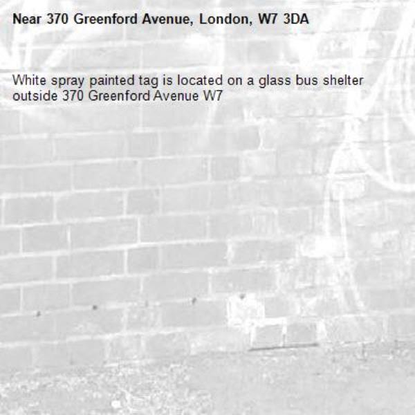White spray painted tag is located on a glass bus shelter outside 370 Greenford Avenue W7 -370 Greenford Avenue, London, W7 3DA
