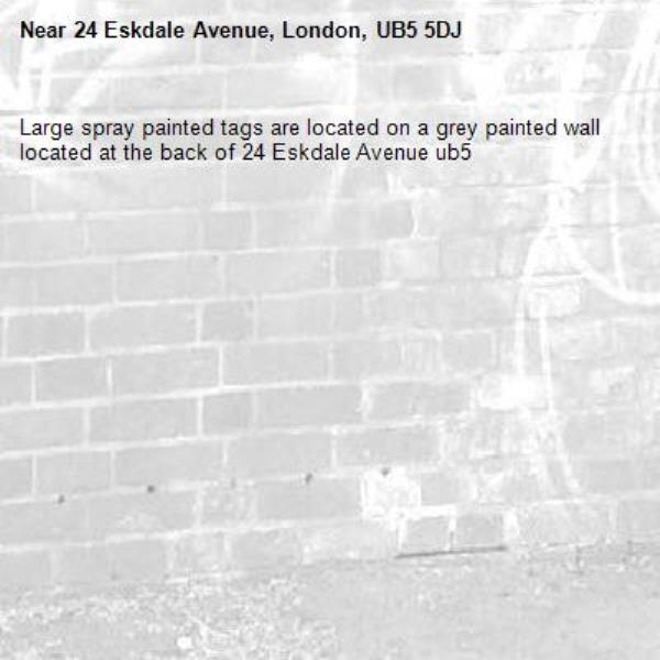 Large spray painted tags are located on a grey painted wall located at the back of 24 Eskdale Avenue ub5-24 Eskdale Avenue, London, UB5 5DJ