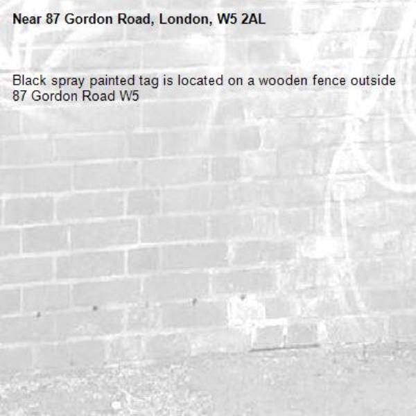 Black spray painted tag is located on a wooden fence outside 87 Gordon Road W5 -87 Gordon Road, London, W5 2AL
