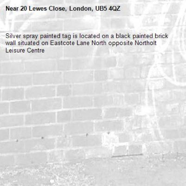 Silver spray painted tag is located on a black painted brick wall situated on Eastcote Lane North opposite Northolt Leisure Centre -20 Lewes Close, London, UB5 4QZ